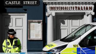 Um policial protege o restaurante de Zizzi onde Sergei Skripal e sua filha Yulia foram envenenados pouco antes de serem encontrados no centro de Salisbury, Grã-Bretanha, 8 de março de 2018.