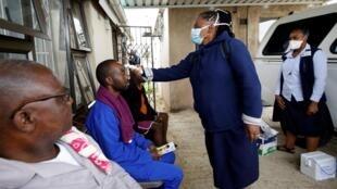 Du personnel soignant prend la température d'habitants d'un township de Durban en Afrique du Sud le 4 avril 2020.