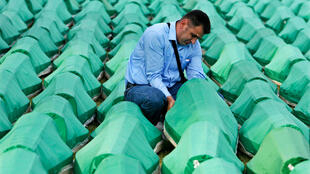 A Muslim man mourns by the coffin of his relative during joint burial in Potocari