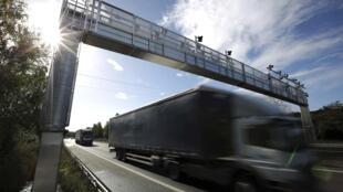 A lorry drives under an ecotax control point at Saint-Sébastien-sur-Loire near Nantes