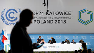 A participant's shilouette is seen during the COP24 UN Climate Change Conference 2018 in Katowice, Poland December 2, 2018.