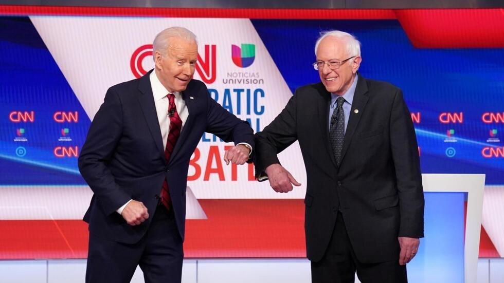 Joe Biden (à gauche) et Bernie Sanders se saluent du coude avant le début de leur débat télévisé. Le 15 mars 2020.