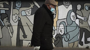 Un hombre con mascarilla y guantes protectores por el coronavirus pasa frente a una pintura mural el 2 de abril de 2020 en la localidad gallega de Bueu, al noroeste de España