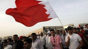 A man holds the Bahraini flag during an anti-government rally by main opposition group Wefaq in Bilad al-Qadeem, west of Manama