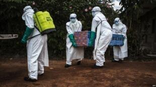 Maafisa wa afya wakibeba mwili wa mgonjwa wa Ebola ambao hajathibitishwa huko Mangina, karibu na Beni, mkoa wa Kivu Kaskazini, Agosti 22, 2018.