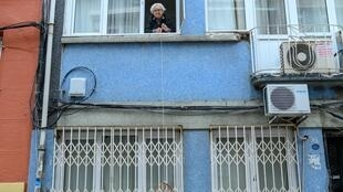 Like other elderly people in Istanbul, Lutfiye Yesilbas, 89, lowers down her basket to receive groceries, after over 65-year olds were confined at home to help protect them from the spread of coronavirus