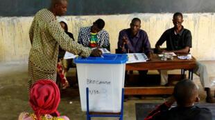 Un homme glisse son bulletin dans l'urne d'un bureau de vote de Bamako, le 12 août, pour le second tour de la présidentielle.