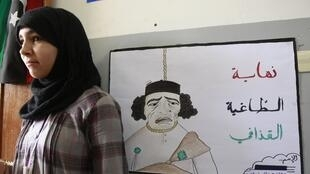 A Libyan girl stands in front a caricature of Moamer Kadhafi in a school in the rebel-held city of Misrata