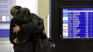 Familiar de vítima do acidente com o Airbus da companhia Metrojet é consolado no aeroporto de São Petersburgo.