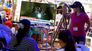 Familiares dos 12 adolescentes bloqueados em caverna na Tailândia assistem ao vídeo feito por mergulhadores, no dia 4 de julho.