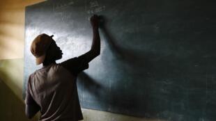 Un élève écrit au tableau de sa classe à Lomé, le 15 avril 2013.