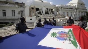 Des policiers haïtiens brandissant le drapeau national devant le palais présidentiel détruit, à Port-au-Prince, le 17 janvier 2010.