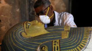 Археолог снимает крышку прекрасно сохранившегося саркофага из Луксорского некрополя, 24 ноября 2018 г.