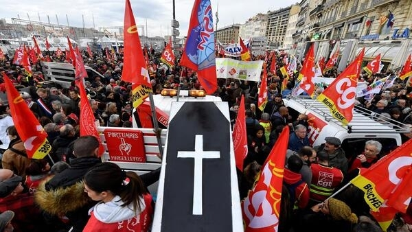 People wave the flags of French trade union General Confederation of Labour (CGT) and carry a mocked coffin as they take part in a demonstration to protest against the pension overhauls, in Marseille, southern France, on December 5, 2019.