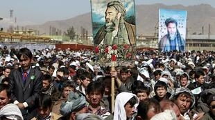 People hold up pictures of Hazara leader Abdul Ali Mazari during a rally to mark the 16th anniversary of his death in Kabul