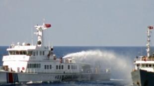 Tàu tuần duyên của Trung Quốc (T) phun vòi rồng xua đuổi tàu hải cảnh của Việt Nam tại khu vực gần quần đảo Hoàng Sa, Biển Đông. (Ảnh chụp ngày 04/05/2014)