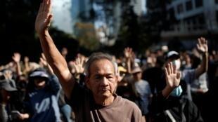 Les manifestants main levée pour écouter l'hymne du mouvement, «Glory to Hong Kong», le 30 novembre dans le centre.