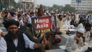 Un homme tient une pancarte «Pendez Asia» lors d'une manifestation le 31 octobre 2018 à Lahore au Pakistan.