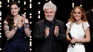 Pedro Almodóvar stands in between Monica Bellucci (L) and Lily-Rose Depp (R) at the opening of the 70th Cannes Film Festival
