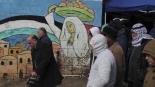 Palestinos caminan frente a un mural en Cisjordania, el 24 de enero de 2020.