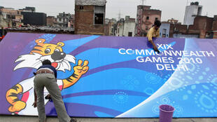 Workers clean a billboard outside the Commonwealth Games athletes village, in New Delhi