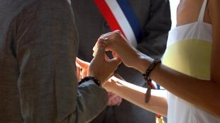"""Un couple de """"pacsés"""" passe, le 11 août 2001, pour la première fois devant le maire du IXe arrondissement de Paris, le """"pionnier"""" Jacques Bravo, qui a inventé, dans sa mairie, une courte cérémonie pour """"faire partager la joie du consentement"""". Le couple av"""