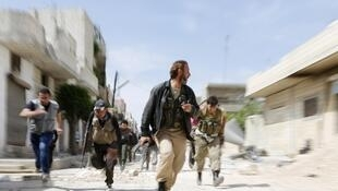 Rebel fighters run to escape sniper fire from the Syrian army. 29 April 2014.