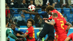 France's Samuel Umtiti scores their first goal during their match against Belgium on 10 July 2018.