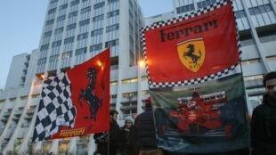Fãs agitam bandeiras da Ferrari em homenagem ao aniversário de 45 anos de Michael Schumacher, em frente ao hospital universitário de Grenoble.