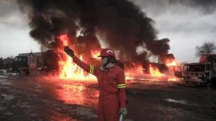 A firefighter in front of burning oil tankers which were attacked and set ablaze by unidentified gunmen, 25 February 2011