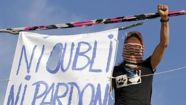 Um ativista ecologista com um cartaz em memória de Rémi Fraisse.