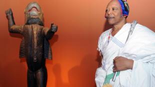 Vua Behanzin của Bénin bên cạnh một bức tượng đầu thế kỷ 19 tại Bảo tàng nghệ thuật nguyên thủy, Quai Branly, Paris ngày 07/04/2010.