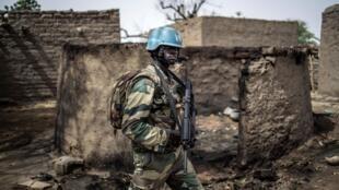 Un soldat de la Minusma marche au milieu du village détruit de Bare le 5 juillet 2019.