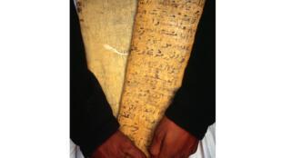 Un libraire de Chinguetti porte des tablettes est sont inscrits des versets du Coran.