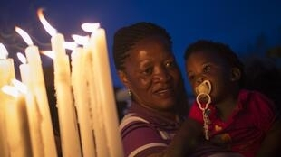 People hold candles in tribute to former South African President Nelson Mandela