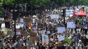 """Jovens ostentam cartazes contra as alterações climáticas durante o protesto das """"sextas-feiras"""" pelo clima, em Paris, no dia 24 de Maio de 2019, no âmbito da campanha mundial da juventude para as eleições europeias."""