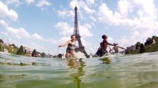 Crianças brincam em chafariz em Paris. Capital francesa registra temperaturas em torno 35°C.