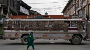 Une femme passe devant un autobus utilisé par les forces de sécurité indiennes comme un barrage routier lors de restrictions après la suppression du statut constitutionnel spécial du Cachemire par le gouvernement, à Srinagar, le 11 août 2019.
