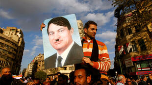 Protester holds a placard depicting Egyptian President Mubarak as Hitler in Cairo's Tahrir Square