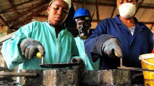 La petite entreprise Binedou Global Service (BGS) en pleine confection de pavés à base de déchets plastiques et de sable.