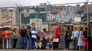 圖為委內瑞拉首都民眾在一家超市前排隊購買食品