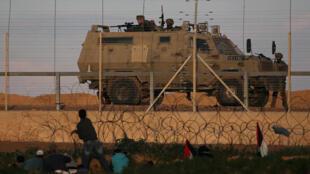 Des manifestants palestiniens face à un blindé israélien à la frontière en Israël et la bande de Gaza, le 18 janvier 2019.