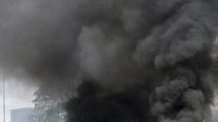 A protester stands near burning tyres at a road block in Abobo, Abidjan