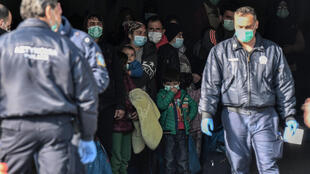 Migrants arrive at the port of Kavala on March 21, 2020, to be transferred to a closed camp in northern Greece as the country battles hard to control the novel coronavirus