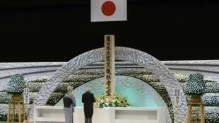 O Imperador Akihito e imperatriz Michiko fazem um minuto de silêncio em frente do memorial que foi montado para relembrar as vítimas do terremoto e tsunami.