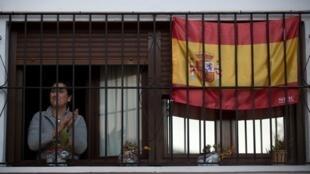 Une femme applaudit à sa fenêtre pour remercier les agents de santé qui travaillent alors que l'ensemble de l'Espagne est confinée, à Ronda, le 3 avril 2020.