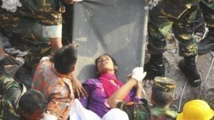 Equipe de resgata transporta mulher encontrada com vida nesta sexta-feira, 10 de maio, dentro do Rana Plaza, prédio que desabou em Bangladesh causando a morte, até agora, de 1035 pessoas.