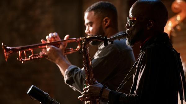 Jowee Omicil on saxophone alongside Ludovic Louis on trumpet