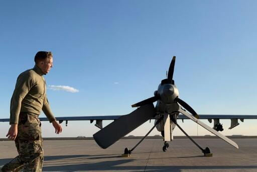 A US soldier walks past a drone at the Ain al-Asad airbase in the western Iraqi province of Anbar