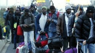 Migrantes cerca de los buses que los conducen a los centros de acogida